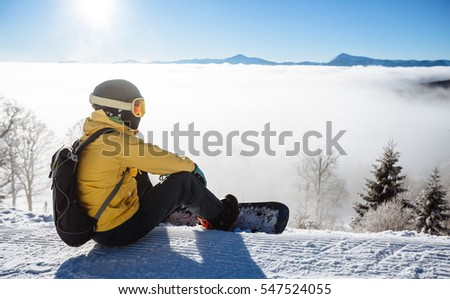 Snowboarder sitting and looking at mountain chain in the background