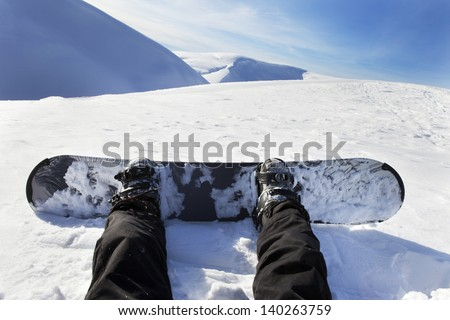Snowboarder sitting on snow in high mountains - stock photo