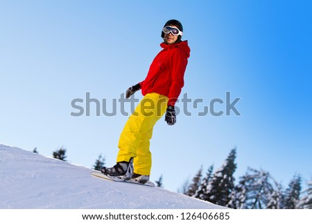 Snowboarder sliding down a slope on a sunny day - stock photo