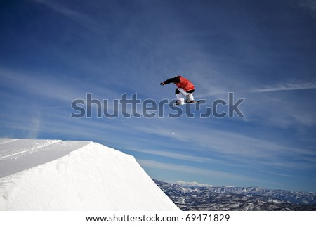Snowboarder spins through the air at winter mountain resort - stock photo