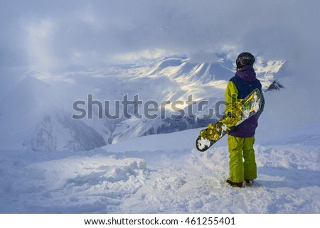 snowboarder standing and looking at the mountains in snowy weather