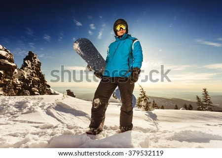 Snowboarder stands on mountain top and sunset backdrop. Sheregesh resort, Siberia, Russia - stock photo