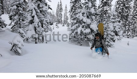 Snowboarder stepping snow with snowshoes in winter forest - stock photo