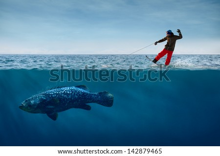 Snowboarder Surfing on Waves with the Fish on a Leash - stock photo