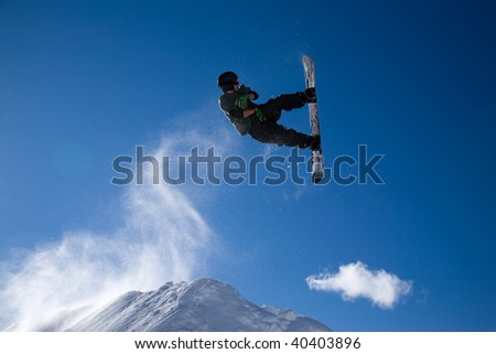snowboarder taking big air jump with bright blue sky