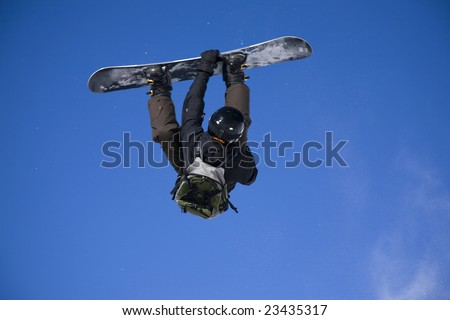 snowboarder taking big air jump with bright blue sky. motion blur - stock photo