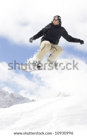snowboarder taking jump in fresh snow - stock photo