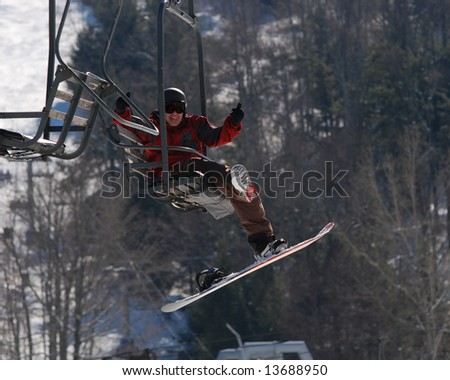 Snowboarder taking the Ski Lift up the Mountain