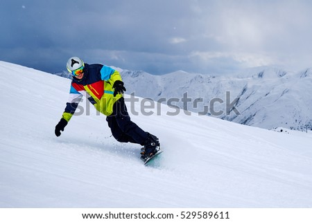 snowboarder turns on a slope against the dark sky with clouds