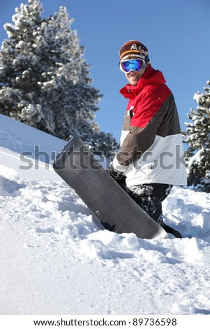 Snowboarder walking up a mountain - stock photo