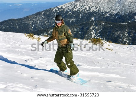 Snowboarder woman on the snow slope under sun - stock photo