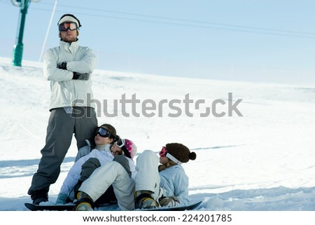 Snowboarders lying in snow, looking up at friend - stock photo