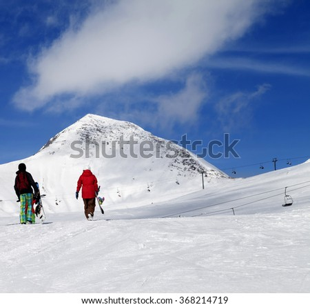 Snowboarders on slope at sun nice day. Caucasus Mountains, Georgia, region Gudauri. - stock photo