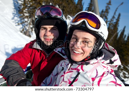 Snowboarders on the chairlift smile for the camera - stock photo