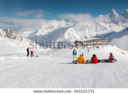 Snowboarders sitting on a ski slope taking a break in front of a mountain hut and high snow covered mountains in Chamonix in the French Alps  Copyspace. - stock photo
