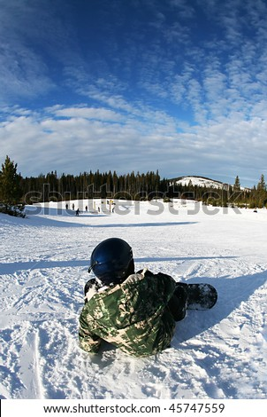 snowboarding boy lying on hill watching skiers - stock photo