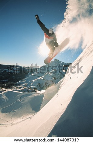 Snowboarding off a cliff off piste on a sunny day in Donner Pass, California, USA - stock photo