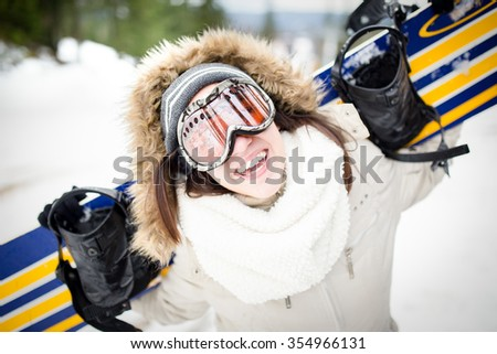 Snowboarding.Young beautiful woman with ski mask holding her snowboard at ski slope Young woman  in ski resort holding snowboard on her shoulders and smiling.Concept of winter holiday  - stock photo