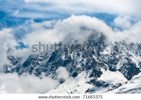 Snowbound mountain peaks in clouds. High Alps.