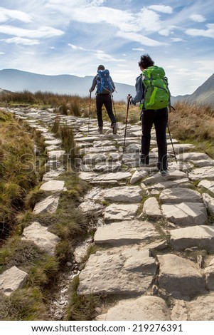 SNOWDONIA PARK, WALES, UK - September 18, 2014: Two hikers on Llanberis path to Snowdon mountain. Llanberis Path is the longest and most gradual of the six main paths to the summit of Snowdon mountain - stock photo