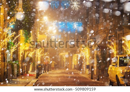 Snowfall at night street with holiday decoration in Parma, Emilia-Romagna, Italy.