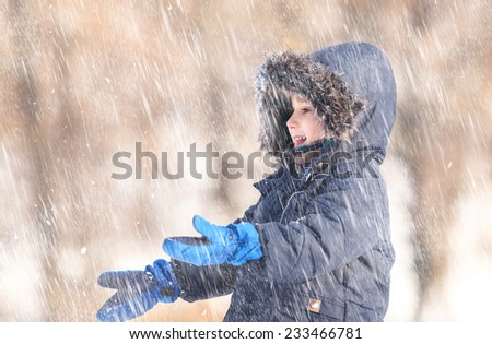 Snowfall. Cute boy in a winter jacket, playing with snowflakes - stock photo