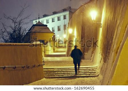 Snowfall in the city - man is walking in narrow street in Prague - stock photo