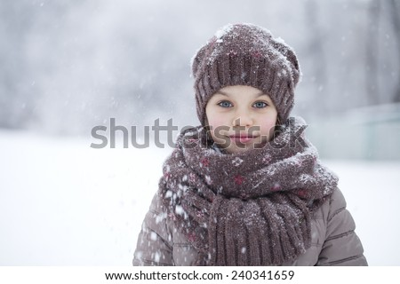 Snowfall, portrait of a happy little girl on the background of a winter park