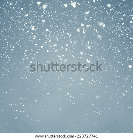 Snowfall with Light Blue Background - Fluffy snowflakes slowly falling in front of a light blue background with vignette - stock photo