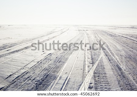 snowfield with tyre traces - stock photo