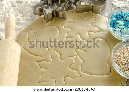 Snowflake and mitten cookie cutters cutting out holiday sugar cookies with wooden rolling pin and white dragees and blue snowflake candy sprinkles