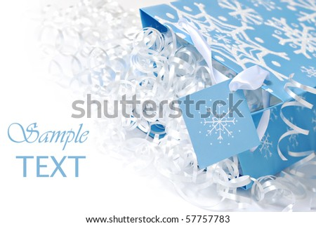 Snowflake gift bag with shiny curling ribbon on white background with copy space.  Macro with shallow dof. - stock photo