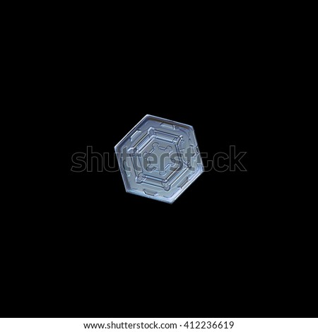 Snowflake isolated on black background: macro photo of real snow crystal, captured on glass surface with LED back light. This is small snowflake of hexagonal plate type with symmetrical pattern inside - stock photo