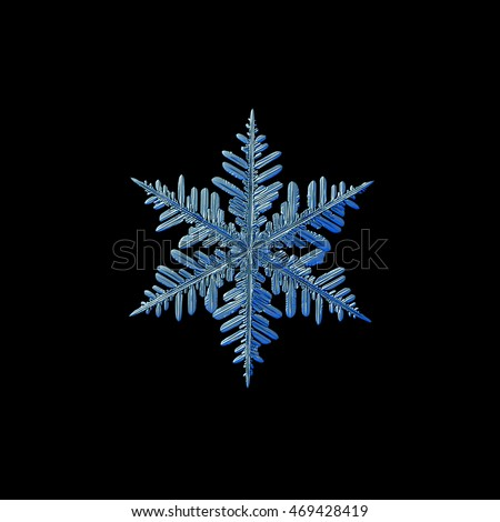 Snowflake isolated on black background. This is macro photo of real snow crystal: big stellar dendrite with complex structure and long arms.