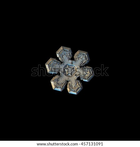 Snowflake isolated on black background. This is macro photo of real snow crystal with relief and glossy surface, and complex inner pattern. Version with warm yellow lighting. - stock photo