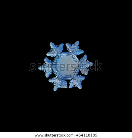 Snowflake isolated on black background. This is real snow crystal, around 3 millimeters from tip to tip, with unusual big, flat and empty central hexagon, relief outer rim and short arms with ridges. - stock photo