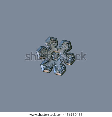 Snowflake isolated on uniform grey background. This is macro photo of real snow crystal with relief and glossy surface, version with silver lighting. - stock photo
