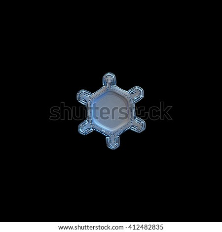 Snowflake isolated on white background: macro photo of real snow crystal, captured on glass surface with LED back light. This turtle-like snowflake contains unusual pattern of tiny dots around center. - stock photo