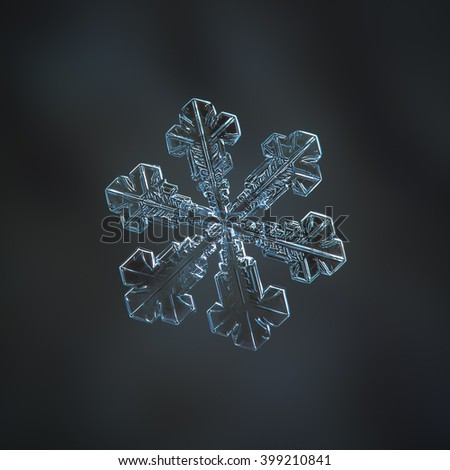 Snowflake on dark grey backdrop: macro photo of real snow crystal on woolen fabric in natural light. Background digitally blurred. This is large snowflake with broad arms.