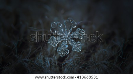 Snowflake on dark textured background, panoramic version: macro photo of real snow crystal on black woolen fabric in natural light. This is big snowflake with simple shape and broad symmetrical arms.