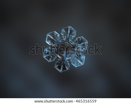 Snowflake on smooth dark cyan background. This is macro photo of real snow crystal with short arms, good symmetry and simple pattern inside of central hexagon.