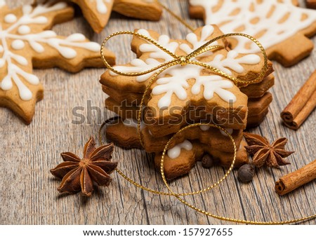 Snowflake shaped gingerbread cookies stacked and tied with a gold bow. - stock photo