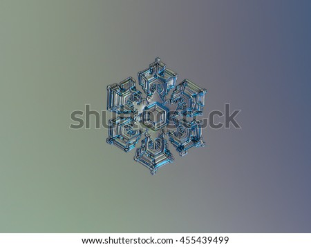 Snowflake with six broad arms and random bubbles of rime on surface, sparkling on smooth gradient background. This is macro photo of real snow crystal, taken on glass surface with back lighting. - stock photo