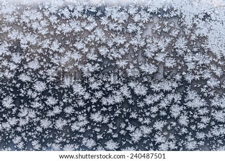 snowflakes and frost on frozen windowpane in cold winter evening close up - stock photo