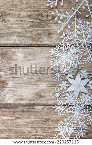 Snowflakes border on grunge wooden background. Winter holidays concept.