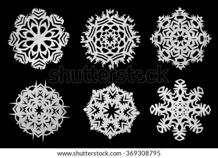 Snowflakes cut out of white paper on a black background - stock photo