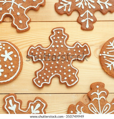 Snowflakes gingerbread cookies on wooden background.