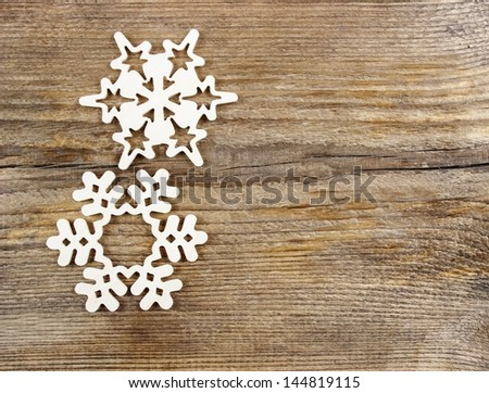 Snowflakes made of wood on wooden background - stock photo