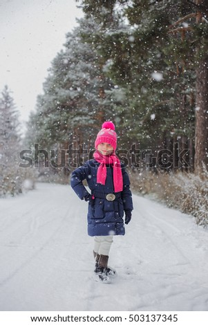 Snowing. Girl walks in the snow-covered forest in autumn day.