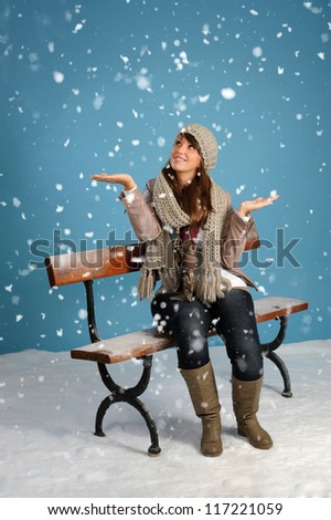 snowing on a woman seated on a bench, blue background - stock photo